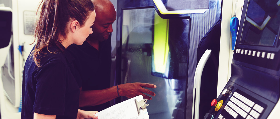An instructor and a student observing a 3D printing machine