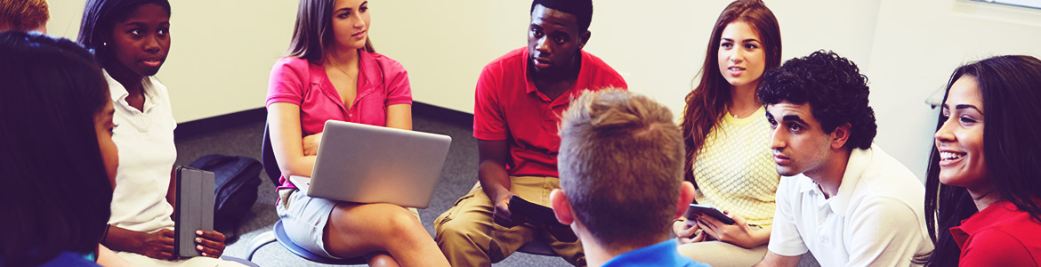A diverse group of students sits in a circle in a group discussion